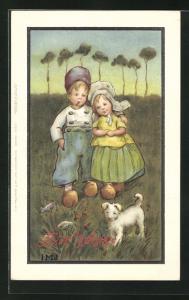 Künstler-AK I.M.J.: Junge und Mädchen in Holzschuhen mit Hund auf einer Wiese