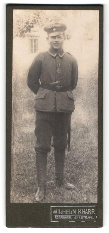 Fotografie Wilhelm Knarr, Rosenheim, Portrait lächelnder Soldat mit Schirmmütze in interessanter Uniform