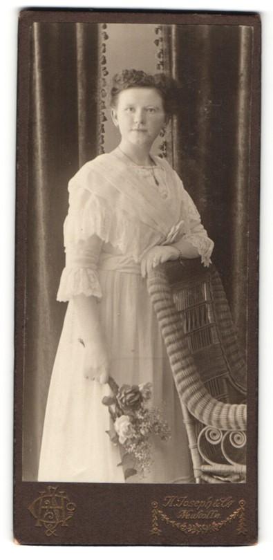 Fotografie H. Joseph & Co, Berlin-Neukölln, Portrait lächelndes hübsches Fräulein im weissen Kleid mit Blumen