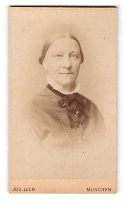 Fotografie Jos. Leeb, München, Portrait betagte Dame mit freundlichem Blick und Schleife am Kragen