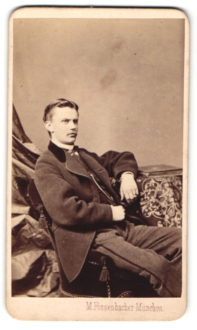 Fotografie M. Pössenbacher, München, Portrait charmanter junger Mann sitzt lässig auf dem Stuhl
