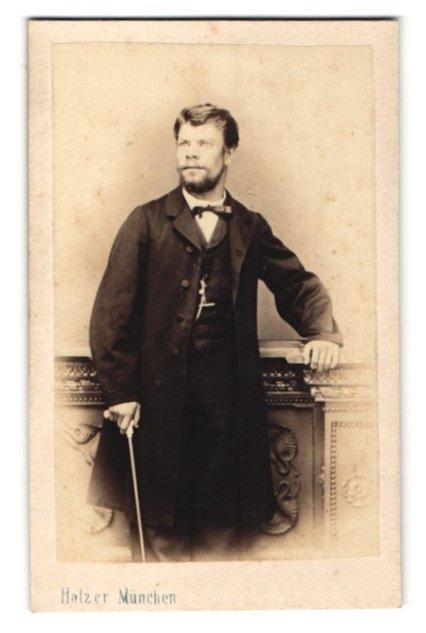 Fotografie Carl Holzer, München, Portrait stattlicher Herr mit Bart und Gehstock im Anzug