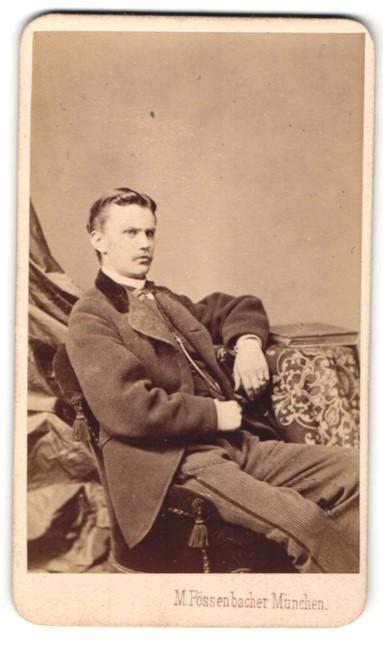 Fotografie M. Pössenbacher, München, Portrait lässig blickender junger Mann im Stuhl sitzend