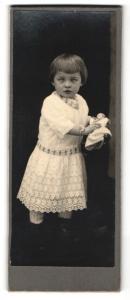 Fotografie Fotograf & Ort unbekannt, niedliches kleines Mädchen mit Puppe und schielendem Blick