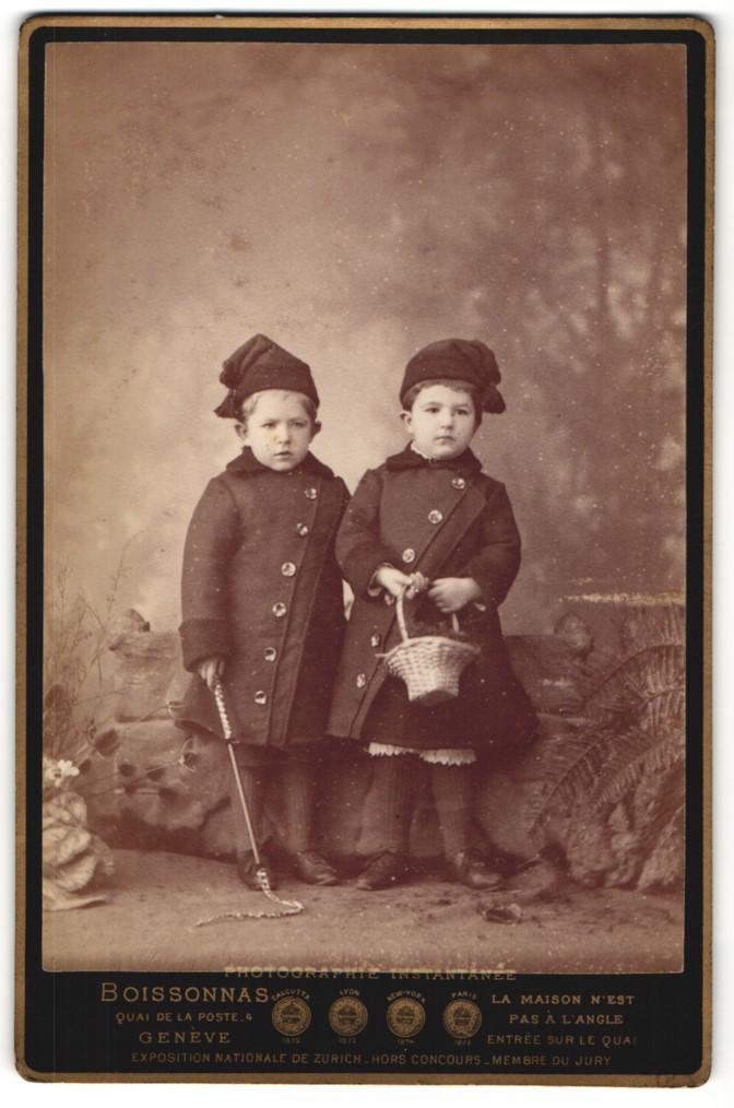 Fotografie Boissonas, Genève, Portrait zwei Kinder in Wintermantel mit Mütze
