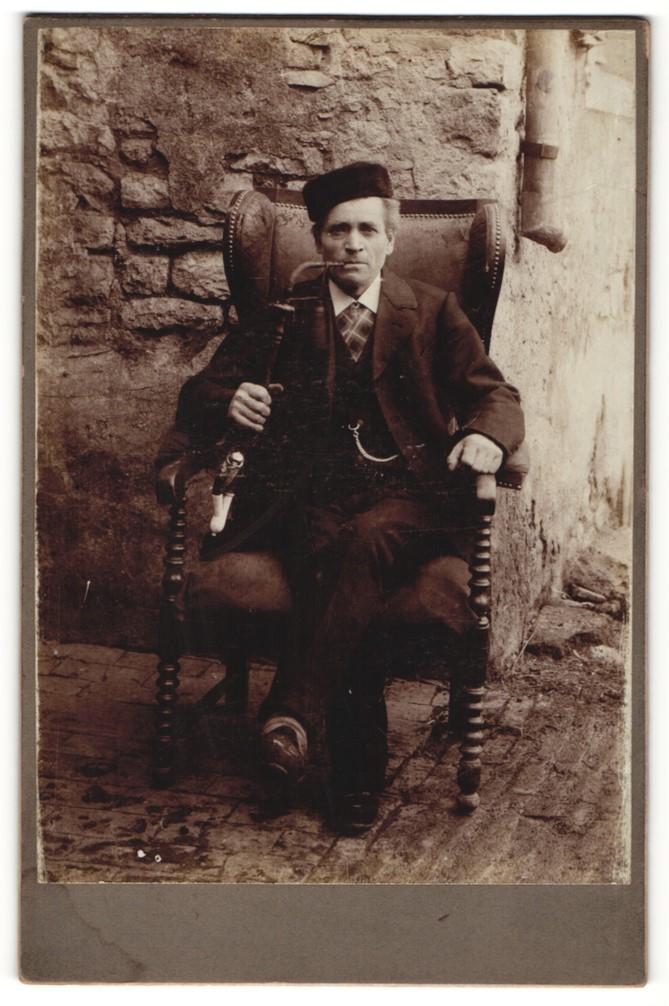 Fotografie unbekannter Fotograf und Ort, Portrait Mann auf Sessel mit Tabakpfeife