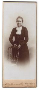 Fotografie Atelier Samson & Co., Würzburg, Portrait junge Dame im eleganten Kleid mit Buch an Stuhl gelehnt