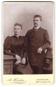 Fotografie A. Fischer, Hannover, Portrait bürgerliches Paar in eleganter Kleidung an Sockel gelehnt