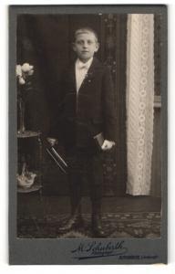 Fotografie M. Schuberth, Kronach, Portrait frecher blonder Bube mit Buch im Anzug