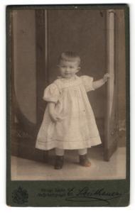 Fotografie E. Scheithauer, Zwickau i. S., Portrait lachendes kleines Mädchen im weissen Kleidchen mit Schnürschuhen