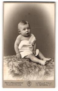 Fotografie Hein & Roggenkamp, Halle / Saale, Portrait niedlicher blonder Bube im weissen Hemdchem auf Fell sitzend