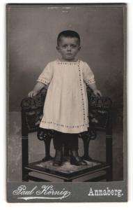 Fotografie Paul Körnig, Annaberg, Portrait zuckersüsses Kleinkind im weissen Hemdchen und Schnürstiefelchen