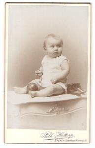 Fotografie Wilh. Holtorp, Bremen, Portrait blondes niedliches Kleinkind mit Bällen im weissen Kleidchen