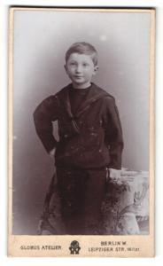 Fotografie Atelier Globus, Berlin, Portrait frech grinsender Bube im schwarzen Anzug