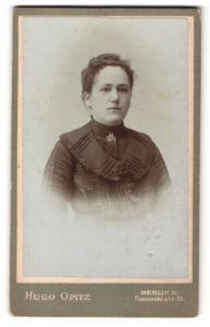 Fotografie Hugo Opitz, Berlin-N, Portrait junge Dame mit Kragenbrosche im eleganten Kleid