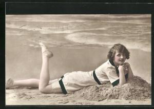 AK Junge Frau im Sand am Strand liegend, Bademode
