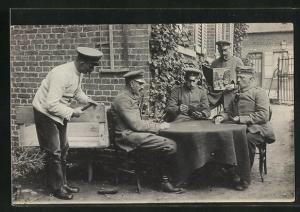 Foto-AK Soldaten in Uniformen im Hof beim Kartenspiel und Zeitung lesend