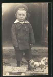 Foto-AK kleiner Bub mit Spielzeugpferd mit Zigarrenkistenkarren