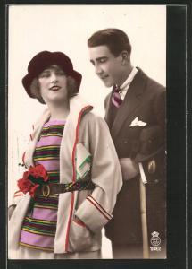 Foto-AK Liebespaar modisch gekleidet, hübsche Frau mit Gürtel und Blumenstrauss