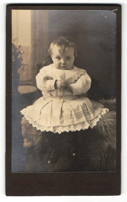 Fotografie Walter Müller, Paderborn, Baby im Kleidchen auf Fell sitzend 0