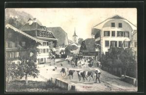 AK Boltigen, Strassenpartie mit Gebäudeansicht und Kühen