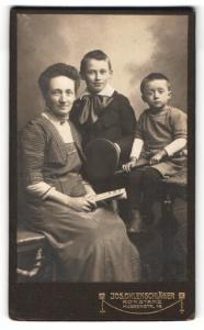 Fotografie Jos. Ohlenschläger, Konstanz, Portrait lächelnde Mutter auf Bank sitzend mit zwei Söhnen