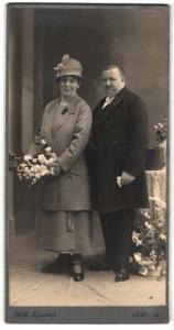 Fotografie Wilhelm Leukert, Leipa i. B., beleibter Mann nebst Dame mit Hut und Blumenstrauss