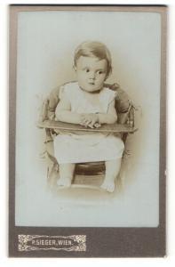 Fotografie Paul Lieger, Wien, Portrait niedliches Kleinkind im weissen Hemd im Hochstuh sitzend