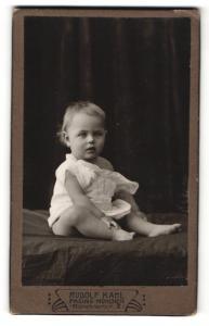 Fotografie Rudolf Kahl, Pasing-München, Portrait niedliches Kleinkind im weissen Hemd auf Laken sitzend