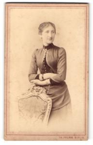 Fotografie Th. Prümm, Berlin, Portrait junge Dame im eleganten Kleid auf Stuhl gestützt