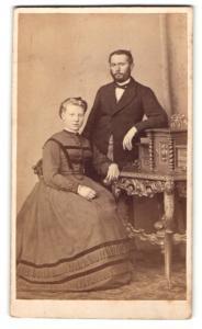 Fotografie Julius Giere, Hannover, Portrait junge Dame im eleganten Kleid am Tisch sitzend u. Herr im Anzug