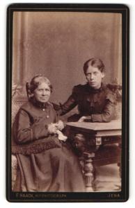 Fotografie F. Haack, Jena, Portrait ältere Dame mit Stricknadeln und junge Dame im eleganten Kleid am Tisch sitzend
