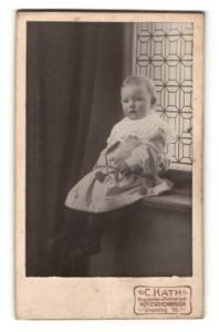 Fotografie C. Kath, Kötzschenbroda, Portrait niedliches blondes Mädchen auf Fensterbank sitzend