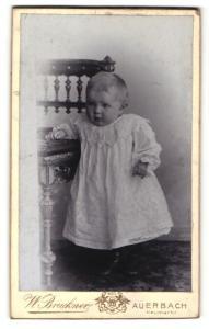 Fotografie W. Bruckner, Auerbach, Portrait süsses blondes Kleinkind im weissen Kleidchen