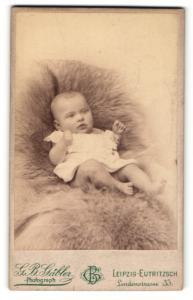 Fotografie G. B. Gäbler, Leipzig-Eutritzsch, Portrait niedliches Baby im weissen Hemdchen auf Fell liegend