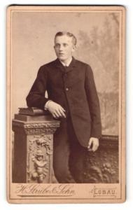 Fotografie H. Strube & Sohn, Löbau, Mann im Mantel und Buch