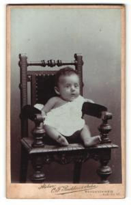 Fotografie Atelier C. F. Beddies & Sohn, Braunschweig, Säugling auf einem hölzernen Stuhl