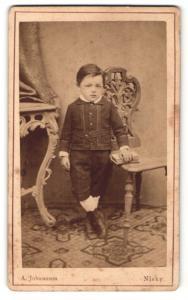 Fotografie A. Johannson, Nisky, Portrait kleiner Junge in hübscher Kleidung mit Buch an Stuhl gelehnt