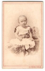 Fotografie Th. Prümm, Berlin, Portrait kleines Mädchen im hübschen Kleid auf Decke sitzend