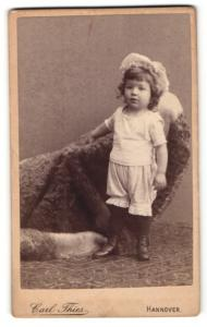Fotografie Carl Thies, Hannover, Portrait niedliches Kleinkind im weissen Hemd an Sessel gelehnt