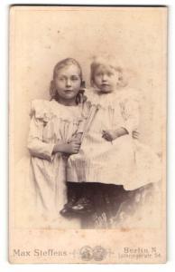Fotografie Max Steffens, Berlin-N, Portrait zwei kleine Mädchen in hübschen Kleidern sich an den Händen haltend