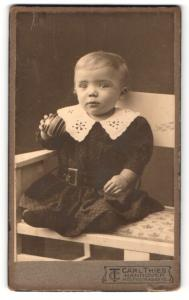 Fotografie Carl Thies, Hannover, Portrait niedliches Kleinkind im hübschen Kleid mit Ball auf Bank sitzend