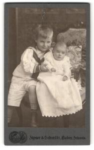 Fotografie Zipser & Schmidt, Baden, Portrait Baby im weissen Kleid u. Bruder im Matrosenanzug auf Sessel sitzend