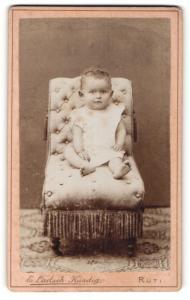 Fotografie E. Laetsch-Kündig, Rüti, Portrait niedliches Kleinkind im weissen Hemd auf Sessel sitzend
