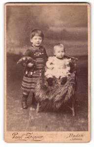 Fotografie Paul Zipser, Baden, Portrait niedliches Kleinkind im hübschen Kleid auf Stuhl sitzend u. Schwester mit Puppe