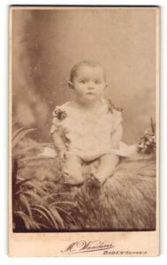 Fotografie M. Wanderer, Baden-Schweiz, Portrait niedliches Kleinkind im weissen Hemd auf Fell sitzend