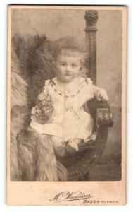 Fotografie M. Wanderer, Baden-Schweiz, Portrait niedliches Kleinkind im weissen Kleid mit Körbchen auf Stuhl sitzend