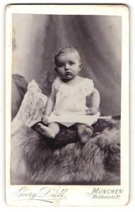 Fotografie Georg Düll, München, Portrait niedliches Kleinkind im weissen Hemd auf Kissen sitzend