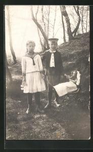 AK Mädchen in Matrosenhemd mit Rock hält Puppenwagen mit Puppe und Junge in Anzug mit Mütze