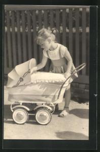 AK kleines Mädchen in kurzen Kleidchen schaut in Kinderwagen